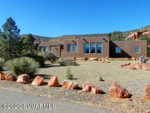 This is a beautiful well-maintained 4 bedroom 3 bath Santa Fe Style home. The unobstructed views out of the huge wall windows expose the red rock views from the living room, great room, kitchen, and breakfast area. Not only are the views stunning but the wildlife that walks up to the great room windows is unbelievable. The 15-foot ceilings in the great room, kitchen, living room and dining room exude elegance, the 3-sided gas fireplace adds to the ambiance in the great room same with the Kiva fireplace in the living room. This home features 3 patios, the front is a spacious outdoor entertaining area with red rock views to watch stunning sunsets, also a fantastic space for star gazing. The smaller back patios have great views of the back plateaus and mature trees. The warm wood ceilings
