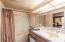 A full size bathroom with a 2-person jetted tub/shower combo, single vanity & mini fridge
