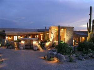 Sunset photo with welcome home lighting and magnificent landscaping.