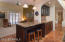 Island with additional storage space, pendant lighting, bar.