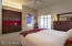 Master bedroom with built in cabinetry, plantation shutters, slider to patio, ceiling fan.