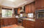 Updated kitchen has custom cherry cabinets, Granite Counters, tile backsplash, breakfast bar, GE Profile appliances & pass-thru to formal dining area.