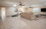 """Expansive living room with 18"""" ceramic tile flooring, upgraded twin ceiling fans, and plantation shutters."""