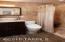 Walk-in shower, stone basin, slab granite, high quality vanity, tile surround, glass tile backsplash, and contemporary faucet.