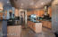 Sleek Black Granite Counters with Stainless Steel Appliances and Hood