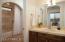 Alder soft-close cabinets, travertine counters and tub surround.
