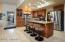 Hickory cabinets with slide-out shelving, slab granite counters, tile backsplash.