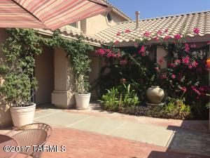 Gated brick courtyard w/mature plants & fountain.