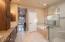 """Custom alder cabinets, 18"""" porcelain tile, glass-enclosure walk-in shower."""