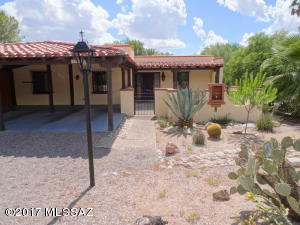 This beautiful home in Catalina Pueblo has tons of curb appeal and great outdoor space, thanks to the enclosed courtyard and covered patio at the front door. Minimal desert landscaping wraps around the home, and the two car carport is seen at left.