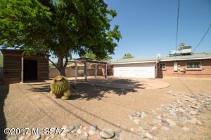 Roomy back yard is fully landscaped with decorative rock and established trees and desert plants.