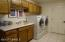 Laundry room with lots of storage cabinets, full size laundry sink and extra counter space.