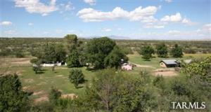 View north of the ranch with old main ranch house behind the 5-ft. masonry wall & surrounded with & assortment of mature shade trees. There are a total of 4BR's & 4BA's (Main house 2BR,1BA & 1 half BA, Studio or guest house with 1BR/1BA, Bunkhouse with 1BR/1BA). Plenty of room for guests, family and friends!