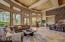 Wall of windows in great room, coffered ceiling, recessed lighting, natural stone flooring