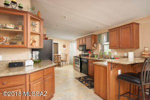 Kitchen with eat in bar and granite counter tops.
