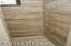 Pebble style shower floor with wood plank walls create an elegant feel.