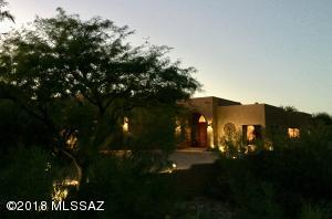 A meandering driveway leads thru natural desert landscape up to the home