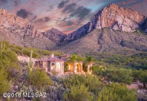 Sitting high up in Guard-gated La Reserve this Impressive Mediterranean 3,623sf 4BR, 3½BA home has Pusch Ridge in your backyard & Oro Valley lights below.