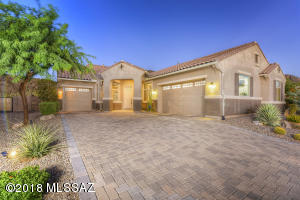 Paver driveway with low care front yard and three car garage