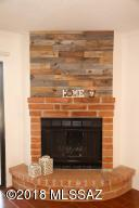 Gorgeous red brick wood burning fireplace with feature wood panel wall above