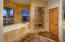 Stone tile surrounds, large soaking tub and separate walk in shower with several shower heads.