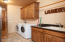 Spacious laundry room with alder wood cabinets, granite counters, sink and plenty of storage