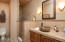 Guest bathroom with beautiful floor to ceiling tile and walk-in shower access from guest bedroom/office and great room