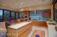 Gourmet kitchen w/glass tile backsplash and custom cabinets.
