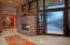 Front entry w/custom glass front door & stone fireplace.