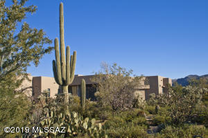 Saguaros and other native plants are nestled around this custom John Herder Building luxury home.