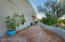 Brick walkway runs entire length of the front and wraps around to patios on south