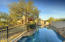 Lap length pool with rock surround, wrought iron fence separates pool area from grass yard