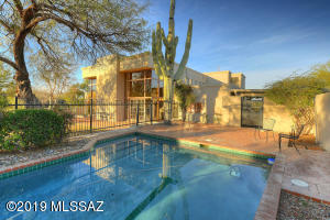 A contemporary Sante Fe hilighted with handcrafted ceilings, brick floors and floor to ceiling windows showering natural light galore . A truly handsome custom home in a serene desert setting.