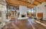 Great Room. 2-story wall of windows faces East. 16' ceilings, massive hand drawn vigas, brick floors. Behind wood door right is entertainment niche.