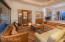 An elegant room for entertaining or relaxing, featuring sliding doors to the patio and the entrance to the wine room.