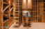 The wine room has a capacity for 2500 bottles, as well as a ladder, cabinets and serving table.