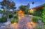 Brick pavers, lush landscaping, night lighting.