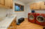 Walk in closet for brooms and cleaning supplies, utility sink, cabinets and counter space.