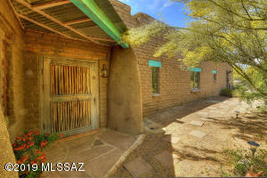 "Front of stabilized mud adobe hacienda layed with 24"" solid walls. Sahuaro ribbed screen door/hand crafted front door"