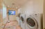 Stone floors, stainless sink, Corian counters & wood cabinets with sorted concealed laundry hampers