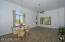 Large living room/dining room features chandeliers and new ceiling fan/light fixture. Brand new wood plank ceramic tiles throughout main floor.