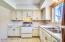 Kitchen features an electric stove, double sink, dishwasher and refrigerator.