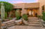 Gracious front entry with double french doors beckoning guests toward the distant Catalina Mountains.