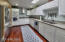 Sleek, large galley kitchen with SS appliances incl hood. Crushed granite counters w/undermount sink, wood floors, recessed lighting. Access to den.