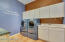 Love this laundry with all of its cabinets, counter tops and storage places. There is even a built in ironing board.