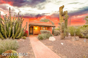 Manicured landscape front yard with brick pavers, natural desert vegetation, covered concrete front patio.
