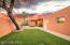 Privacy wall, artificial grass, mature mesquite tree, raised flower beds, graded and drainage.