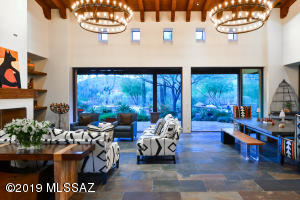 Dramatic Living & Dining Area with wall of windows that open to large covered patio and stunning yard with pool.