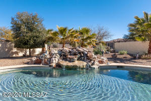 stunning resort-style pebble tec pool and tranquil waterfall with mature landscaping.