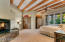 The private master suite with beautiful views north toward the pool and Catalina Mountains is accessed through double custom doors. To one side is the sleeping area and to the other side, divided by the see-through fireplace is the study/den/exercise area.